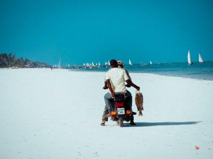 Rollerfahrer am Strand von Matemwe